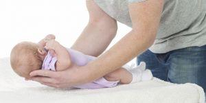 Tata podnosi dziecko potrzymując główkę