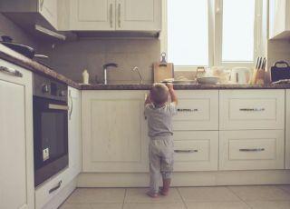 2-letni chłopiec sam w domu próbuje zdjąć coś z kuchennej szafki