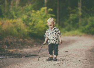 Chłopiec bawi się na leśnej ścieżce