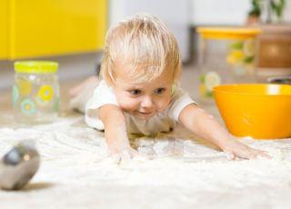 Chłopiec bawi się na podłodze w kuchni