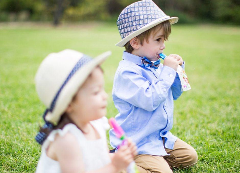 chłopiec i dziewczynka piją musy z torebek wielorazowych z rurką