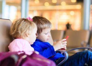 Chłopiec i dziewczynka siedzą wpatrzeni w ekran smartfonu