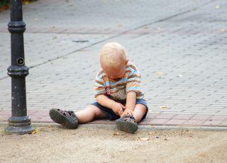 Chłopiec siedzi samotnie na chodniku