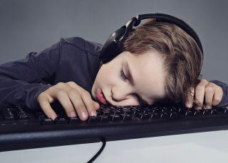 Chłopiec śpi na klawiaturze przy komputerze