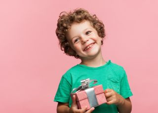 chłopiec trzyma prezent zachwycony