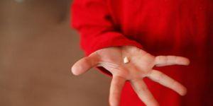 Chłopiec trzyma w ręce mleczny ząb
