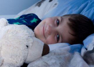 Chłopiec w piżamie przytula maskotkę i idzie spać