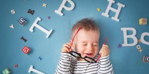 Chłopiec wśród literek uczy się mówić