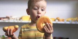 Chłopiec zastanawia się co zjeść: rogalika czy donuta
