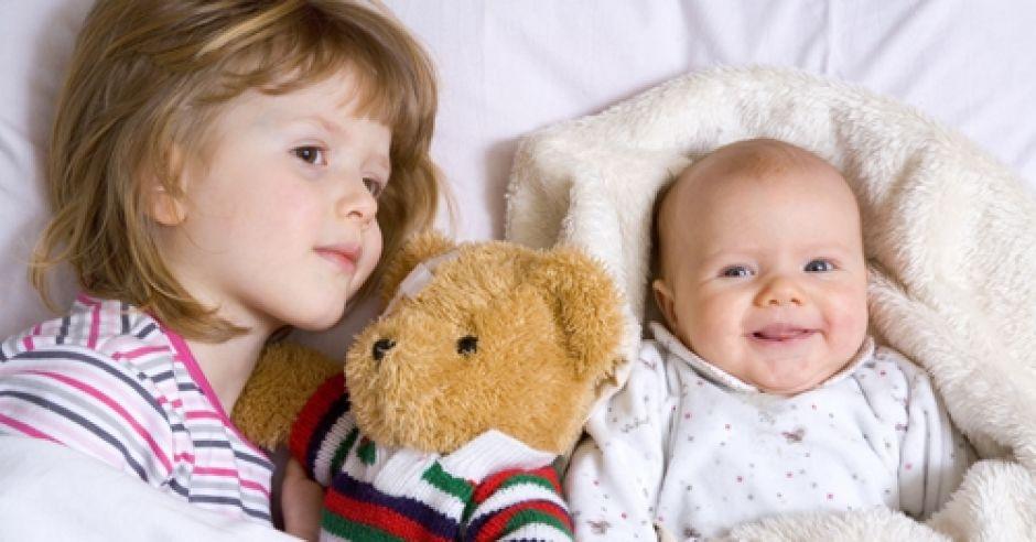 Chore rodzeństwo razem w łóżku z misiem