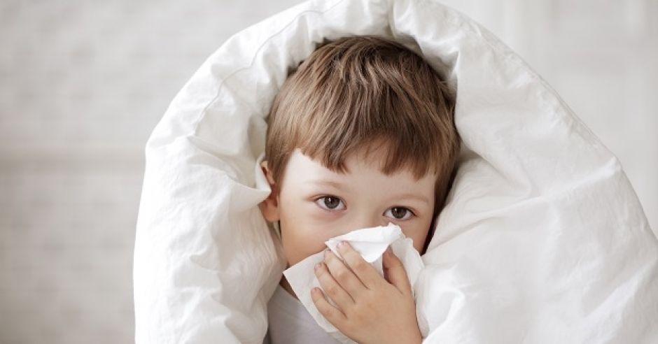 Chory chłopiec leży w łóżku i czyści nos