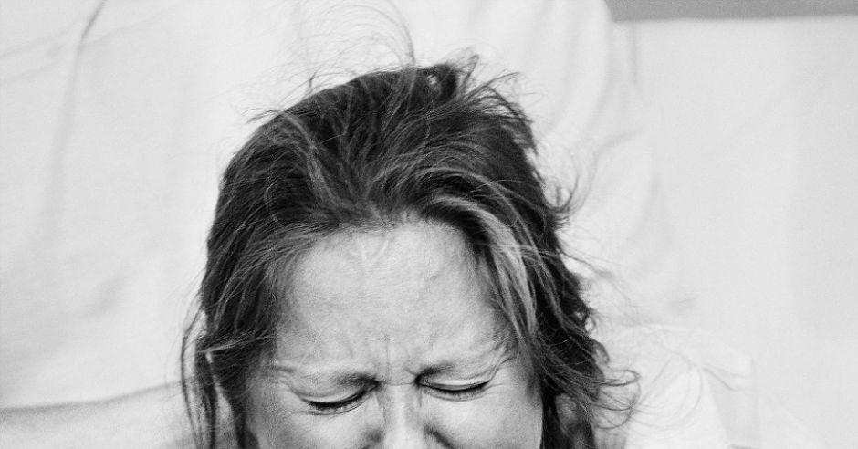 Czarno-biała fotografia twarzy rodzącej kobiety.
