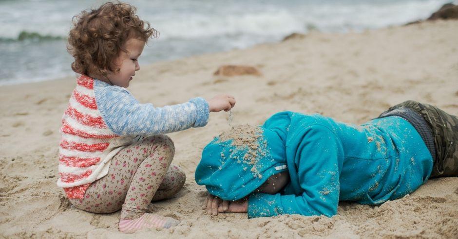 dzieci bawią się na wietrznej plaży