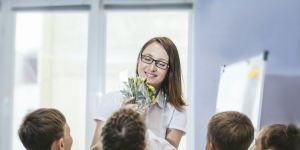 dzieci dają kwiaty ulubionej nauczycielce