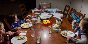 Dzieci jedzą kolację wśród zabawek
