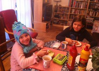 Dzieci w czapkach jedzą śniadanie