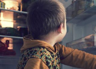 Dziecko bawi się przy lodówce w kuchni