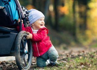dziecko chce stanąć trzymając się wózka