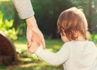 Dziecko idzie na spacer z rodzicem za rękę