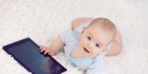 dziecko z tabletem na dywanie