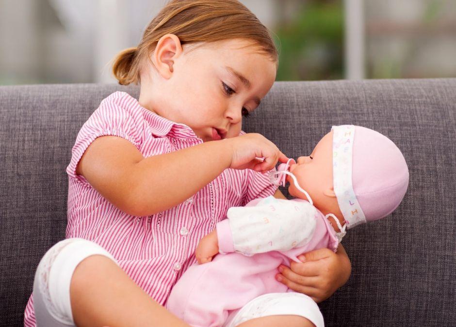 dziewczynka bawi się lalką na kanapie