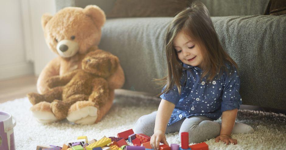 """Dziewczynka bawi się na podłodze i siedzi w niebezpiecznej pozycji """"W"""""""