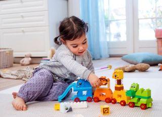 dziewczynka bawi się pociągiem ze zwierzątkami Lego Duplo