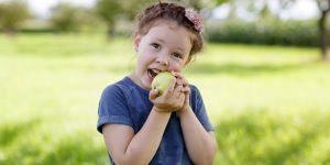 Dziewczynka je brudne jabłko