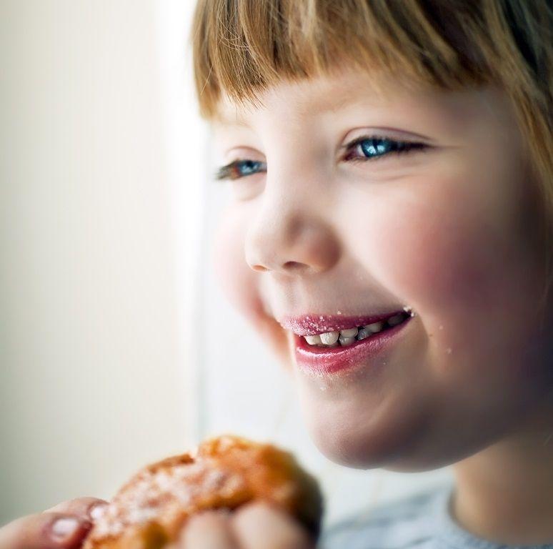 Dziewczynka je pączka z uśmiechem