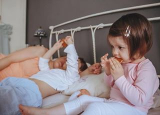 Dziewczynka je śniadanie w łóżku