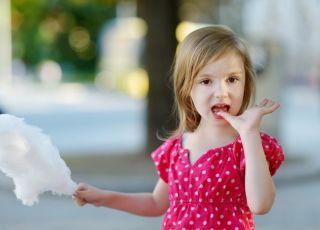 Dziewczynka je watę cukrową i oblizuje palce