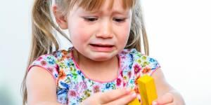 dziewczynka płacze bawiąc się klockami