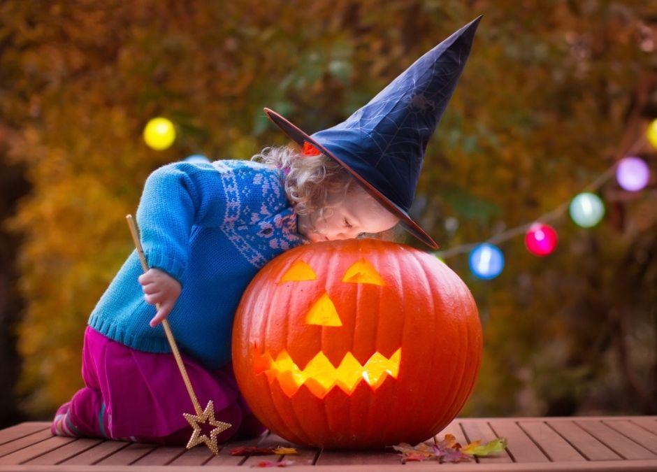 dziewczynka przebrana za czarownicę zagląda do dyni