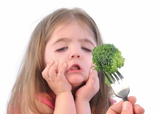Dziewczynka robi śmieszną minę na widok brokułów
