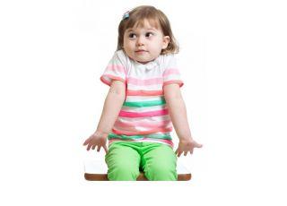 Dziewczynka siedzi na krześle i wzrusza ramionami