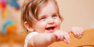 Dziewczynka stoi w łóżeczku i uśmiecha się