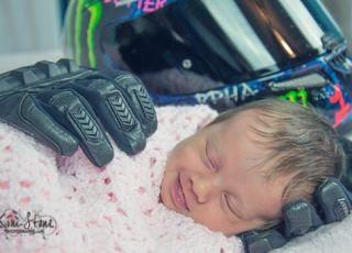 Dziewczynka uśmiecha się leżąc w rękawicach motocyklowych taty