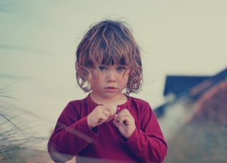 Dziewczynka w czerwonej bluzce bawi się źdźbłem trawy
