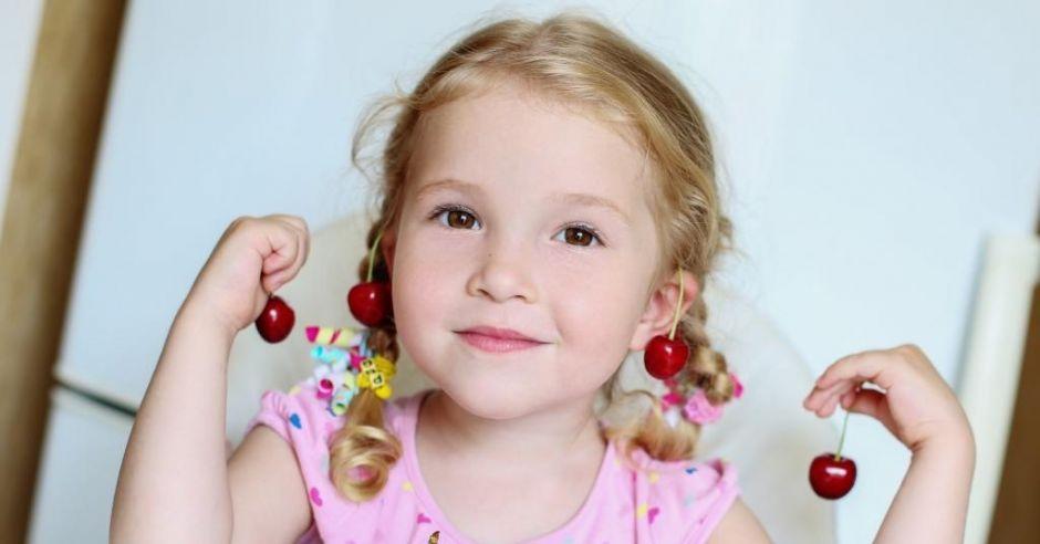 Dziewczynka w kolczykach zrobionych z czereśni