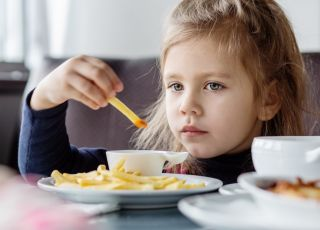 dziewczynka w restauracji je frytki