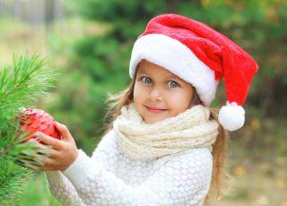 dziewczynka wiesza bombkę na choinkę