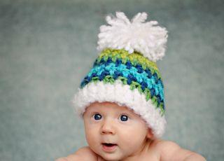 Gołe niemowlę z wielką, ciepłą czapką