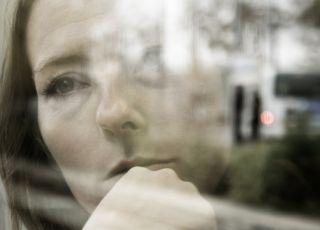 smutna kobieta wygląda przez okno