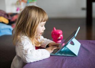 Kilkuletnia dziewczynka bawi się tabletem