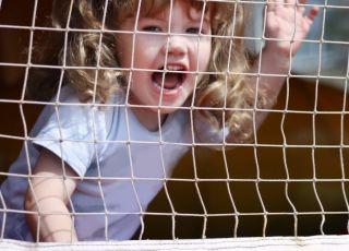 Kilkuletnia dziewczynka bawi się w dmuchanym zamku