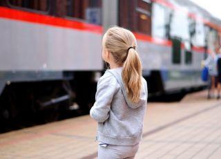 Kilkuletnia dziewczynka na stacji kolejowej