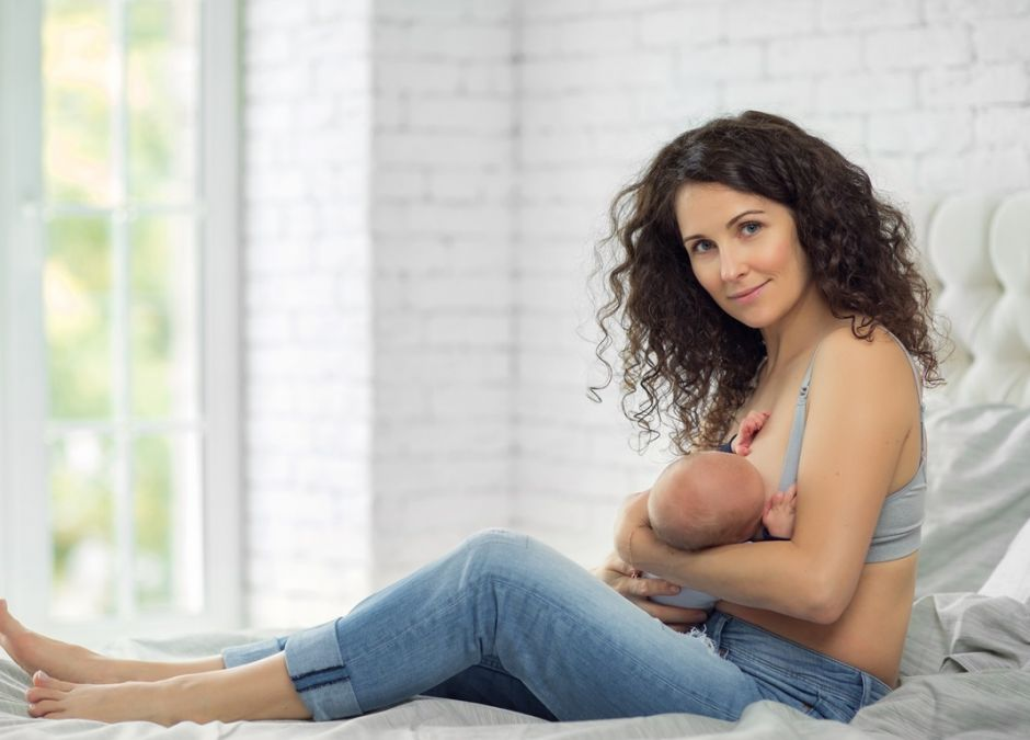 kobiet karmi dziecko piersią siedząc na łóżku