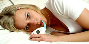 temperatura ciała a dni płodne - kobieta sprawdza temperaturę