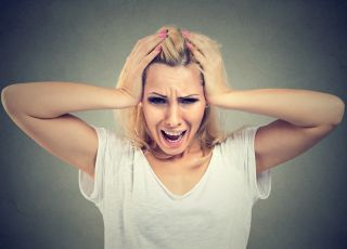 kobieta krzyczy i trzyma się za głowę