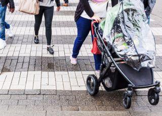 Kobieta prowadzi wózek na przejściu dla pieszych
